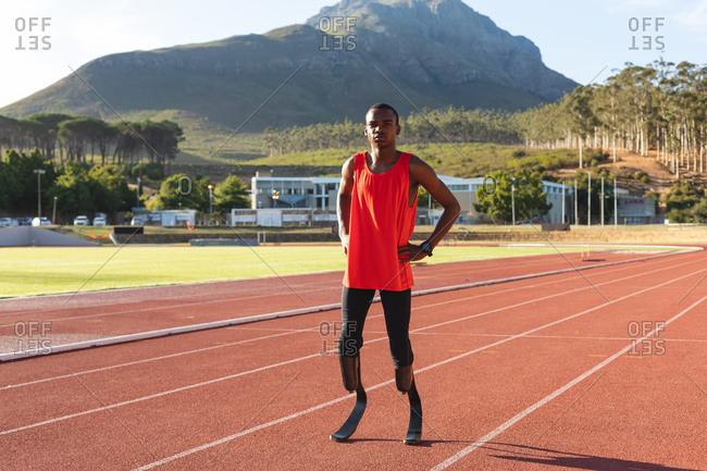 Portrait of fit, mixed race disabled male athlete at an outdoor sports stadium, standing with hands on hips on race track wearing running blades. Disability athletics sport training.