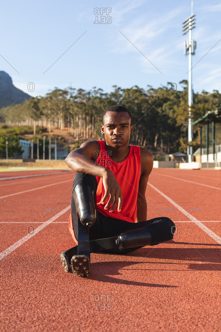 Portrait of fit, mixed race disabled male athlete at an outdoor sports stadium, sitting on race track wearing running blades. Disability athletics sport training.