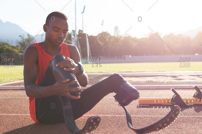 Fit, mixed race disabled male athlete at an outdoor sports stadium, sitting on race track adjusting running blades. Disability sport training.