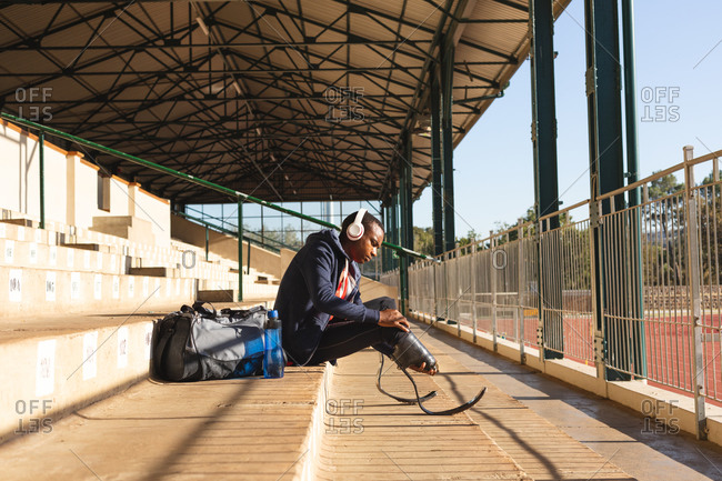 Fit, mixed race disabled male athlete at an outdoor sports stadium, sitting in the stands wearing headphones adjusting running blades. Disability athletics sport training.