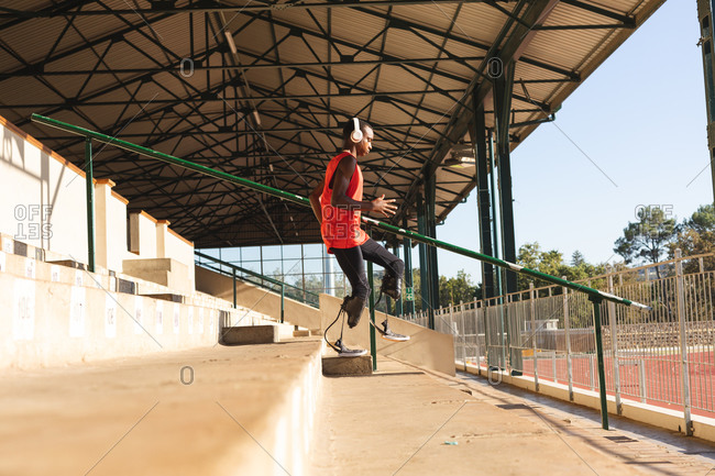 Fit, mixed race disabled male athlete at an outdoor sports stadium, running down stairs in the stands wearing headphones and running blades. Disability athletics sport training.