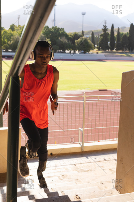 Fit, mixed race disabled male athlete at an outdoor sports stadium, running up stairs in the stands wearing headphones and running blades. Disability athletics sport training.