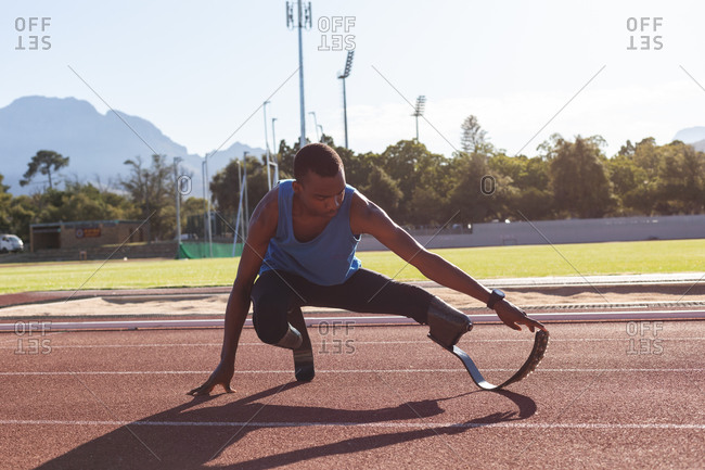 Fit, mixed race disabled male athlete at an outdoor sports stadium, preparing before workout stretching on race track wearing running blades. Disability athletics sport training.
