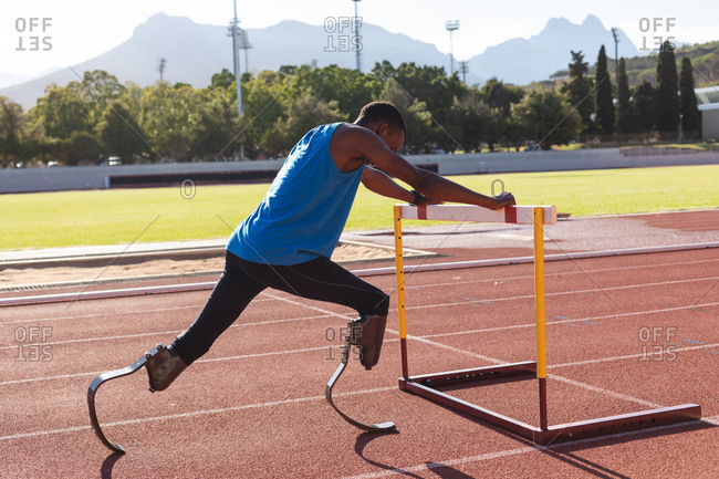 Fit, mixed race disabled male athlete at an outdoor sports stadium, preparing before workout stretching on hurdle on race track wearing running blades. Disability athletics sport training.