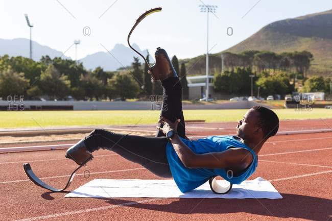 Fit, mixed race disabled male athlete at an outdoor sports stadium, preparing before workout stretching on roller on race track wearing running blades. Disability athletics sport training.