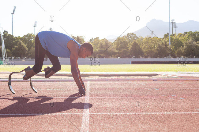 Fit, mixed race disabled male athlete at an outdoor sports stadium, starting a race on race track wearing running blades. Disability athletics sport training.