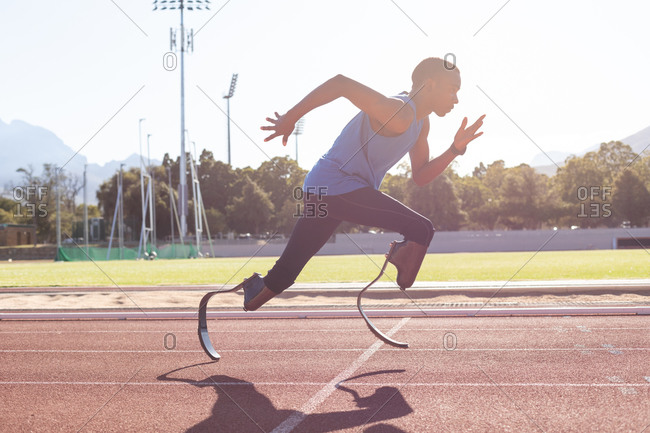 Fit, mixed race disabled male athlete at an outdoor sports stadium, running on race track wearing running blades. Disability athletics sport training.