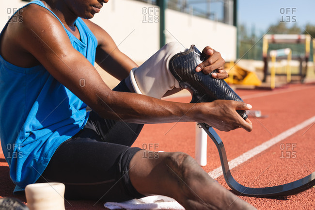 Mid section of fit, mixed race disabled male athlete at an outdoor sports stadium, sitting on race track preparing running blades before workout. Disability athletics sport training.