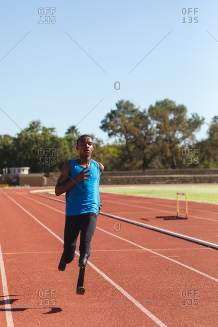 Fit, mixed race disabled male athlete at an outdoor sports stadium, running on race track on running blades. Disability sport training.