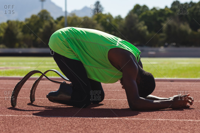 Fit, mixed race disabled male athlete at an outdoor sports stadium, kneeling on race track after a race wearing running blades. Disability athletics sport training.