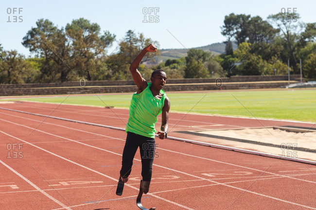 Fit, mixed race disabled male athlete at an outdoor sports stadium, on race track after a race with arms in the air wearing running blades. Disability athletics sport training.