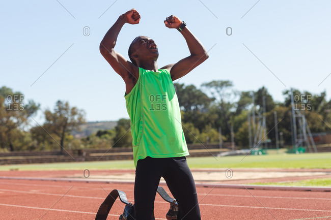 Fit, mixed race disabled male athlete at an outdoor sports stadium, kneeling on race track after race with arms in the air wearing running blades. Disability athletics sport training.
