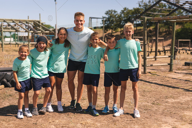 Portrait of a happy group of Caucasian boys and girls and a Caucasian male fitness coach having fun together at a boot camp on a sunny day, with arms around each other, smiling to camera