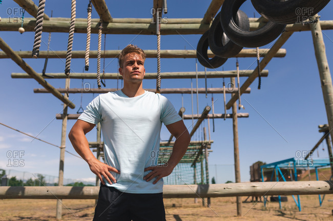 Caucasian male fitness coach at a boot camp on a sunny day, standing with hands on hips under the climbing frame of a jungle gym with hanging ropes