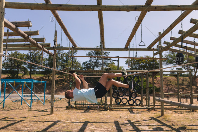 Caucasian male fitness coach at a boot camp on a sunny day, hanging upside down holding a rope with his hands and legs on a jungle gym