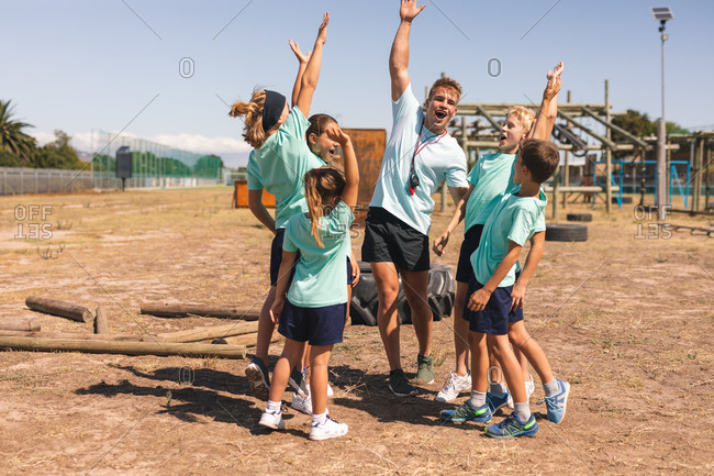 A happy group of Caucasian boys and girls and a Caucasian male fitness coach having fun together at a boot camp on a sunny day, shouting for motivation and smiling with arms in the air