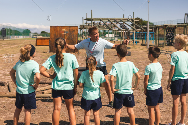 A group of Caucasian boys and girls listening to instructions from a Caucasian male fitness coach at a boot camp on a sunny day, standing and paying attention to him while he gestures and explains