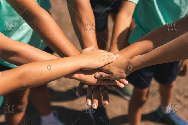 Mid section of a group of Caucasian boys and girls at a boot camp on a sunny day, bonding and stacking hands together before doing an obstacle course, all wearing green t shirts and black shorts