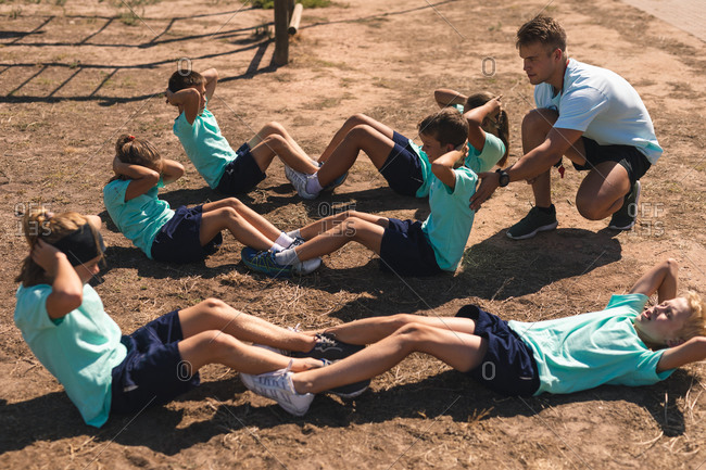 A Caucasian male fitness coach kneeling and instructing a group of Caucasian boys and girls at a boot camp on a sunny day, doing crunches, or sit ups, all wearing green t shirts and black shorts