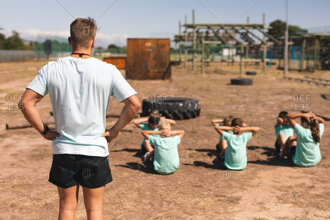 Rear view of Caucasian male fitness coach standing watching a group of Caucasian boys and girls at a boot camp on a sunny day, doing crunches, or sit ups, all wearing green t shirts and black shorts