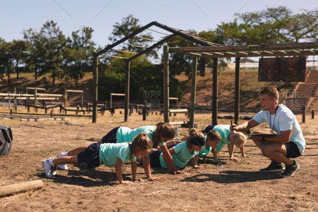 A Caucasian male fitness coach squatting and instructing a group of Caucasian boys and girls at a boot camp on a sunny day doing push ups, all wearing green t shirts and black shorts
