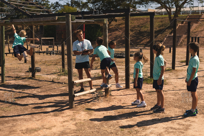 A Caucasian male fitness coach instructing a group of Caucasian boys and girls at a boot camp on a sunny day all wearing green t shirts and black shorts, climbing on a jungle gym and using monkey bars