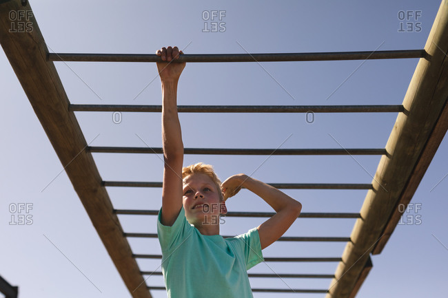 Smiling Caucasian boy with blonde hair at a boot camp on a sunny day, wearing green t shirt, on a jungle gym hanging from the monkey bars against a blue sky