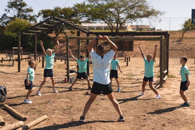 Rear view of Caucasian male fitness coach instructing a group of Caucasian boys girls at a boot camp on a sunny day doing jumping jacks wearing green t shirts and black shorts