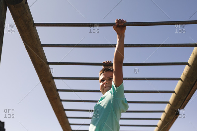 Smiling Caucasian boy with brown hair at a boot camp on a sunny day, wearing green t shirt, on a jungle gym hanging from the monkey bars against a blue sky