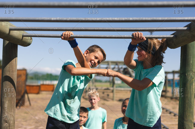 Two smiling Caucasian boys at a boot camp on a sunny day, standing beside each other holding on to the monkey bars, smiling and fist bumping, wearing green t shirts and black shorts