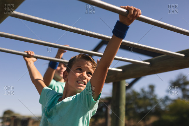 Smiling Caucasian boy with brown hair at a boot camp on a sunny day, wearing green t shirt, on a jungle gym hanging from the monkey bars against a blue sky, another boy behind him in the background