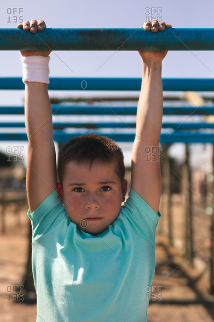 Portrait of Caucasian boy with short dark hair at a boot camp on a sunny day, wearing green t shirt and white sweatband on his wrist, on a jungle gym hanging from the monkey bars against a blue sky