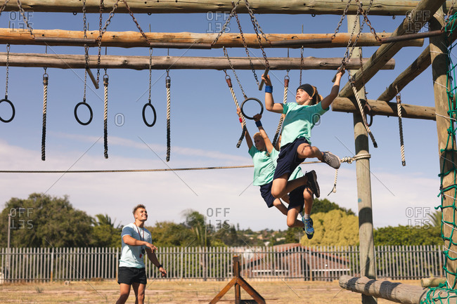 A Caucasian male fitness coach instructing two Caucasian boys at a boot camp on a sunny day, wearing green t shirts and black shorts, climbing on a jungle gym and hanging from rings