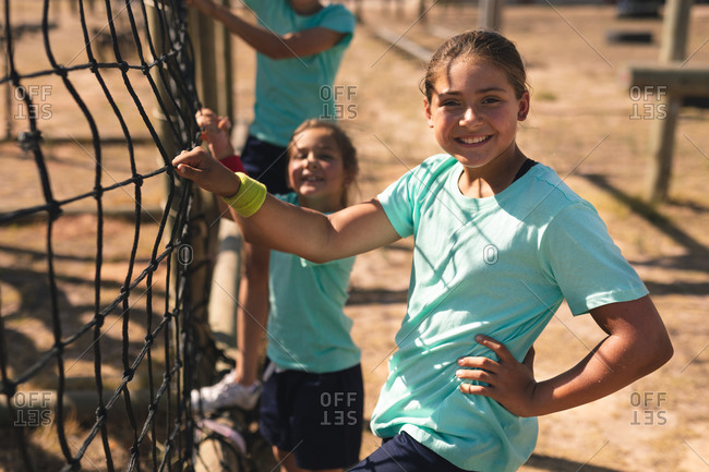Portrait of Caucasian girl at a boot camp on a sunny day, holding onto a net on a climbing frame and smiling to camera, wearing sweatband, green t shirt and black shorts, with kids in the background