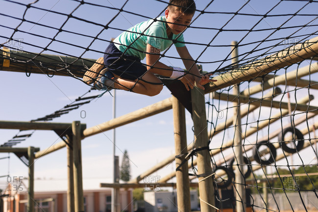Caucasian boy at a boot camp on a sunny day, climbing across a net on a climbing frame, wearing a white sweatband, green t shirt and black shorts