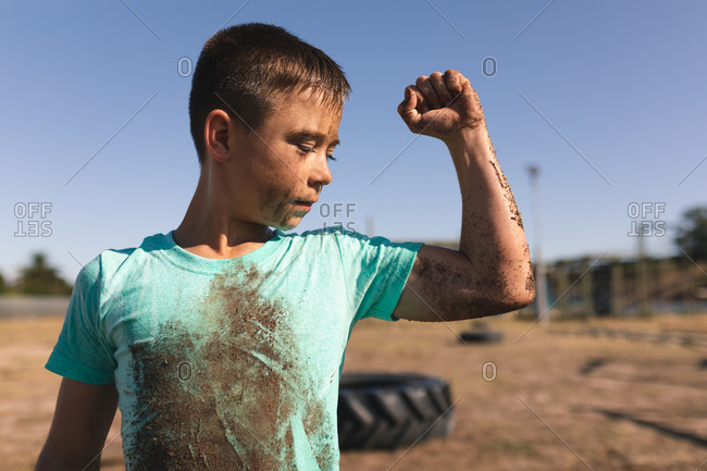 Caucasian boy with short dark hair at a boot camp on a sunny day, with mud on his face and arm and wearing a dirty green t shirt, looking at his arm and flexing his bicep