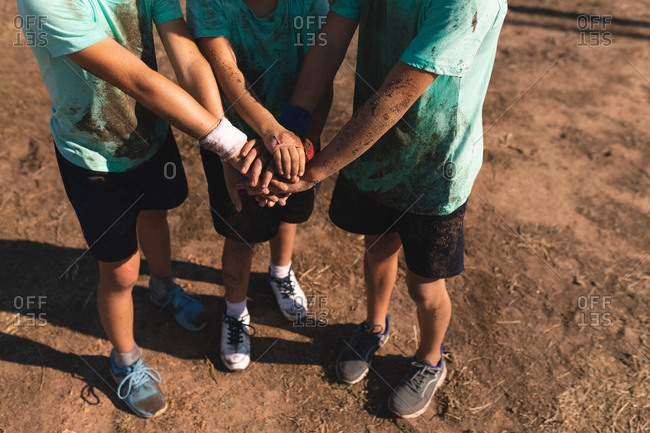 Low section of a group of three Caucasian boys at a boot camp on a sunny day, bonding and stacking hands together before doing an obstacle course, all wearing green t shirts and black shorts