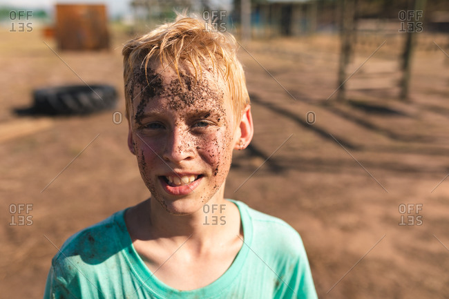 Portrait of happy Caucasian boy with short blonde hair at a boot camp on a sunny day, with mud on his face wearing a dirty green t shirt, looking at camera and smiling