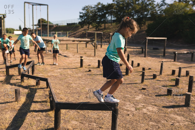 Caucasian girl at a boot camp on a sunny day, wearing green t shirt and black shorts, balancing and walking along a beam on an obstacle course, with other kids following her in the background