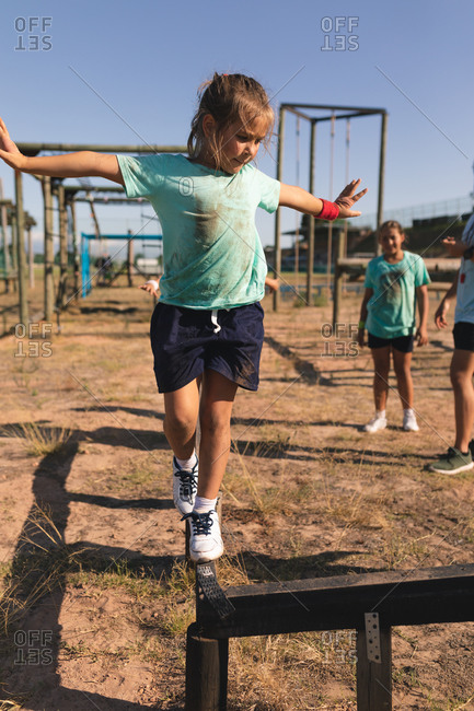 Caucasian girl at a boot camp on a sunny day, wearing green t shirt and black shorts, balancing and walking along a beam on an obstacle course with arms outstretched, with kids in the background