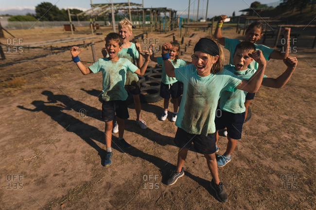 A group of Caucasian boys and girls at a boot camp on a sunny day, wearing dirty green t shirts and with mud on their faces, shouting and flexing their biceps