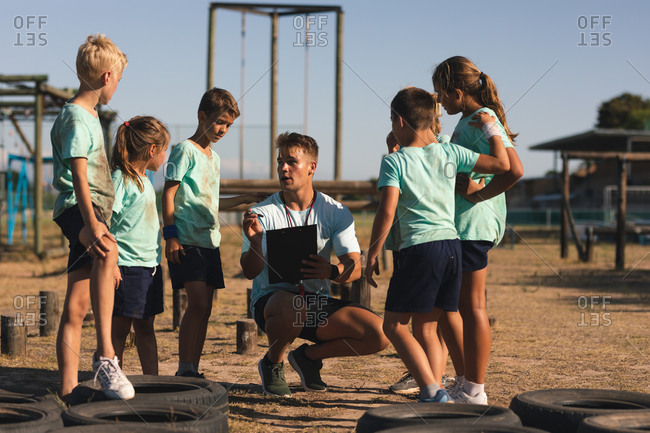 A group of Caucasian boys and girls listening to instructions from a Caucasian male fitness coach at a boot camp on a sunny day, standing and paying attention to him while he squats down and explains