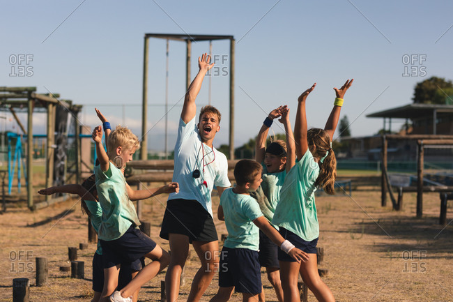 A group of Caucasian boys and girls and a Caucasian male fitness coach at a boot camp on a sunny day, standing and celebrating, shouting with arms raised in the air at the end of an obstacle course