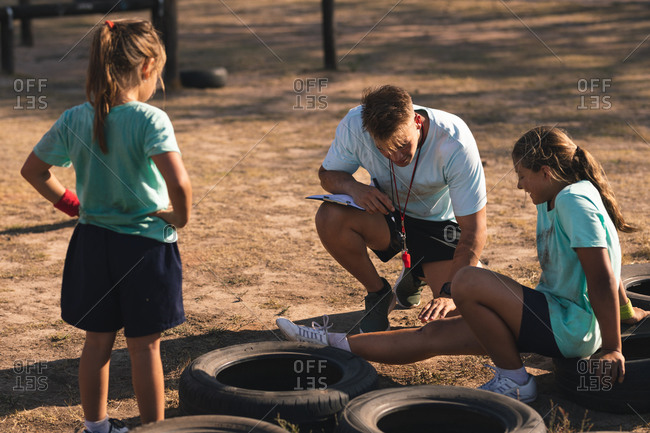 A Caucasian male fitness coach squatting and tending to the injured leg of a Caucasian girl sitting on a tire at a boot camp on a sunny day, with another girl looking on