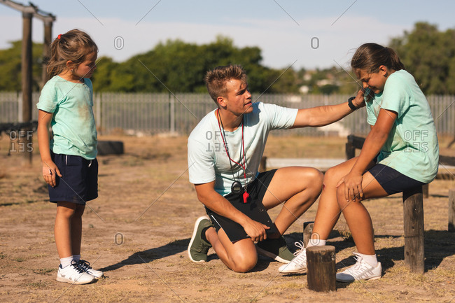 A Caucasian male fitness coach kneeling and comforting a Caucasian girl with an injured leg, sitting at a boot camp on a sunny day, with another girl looking on