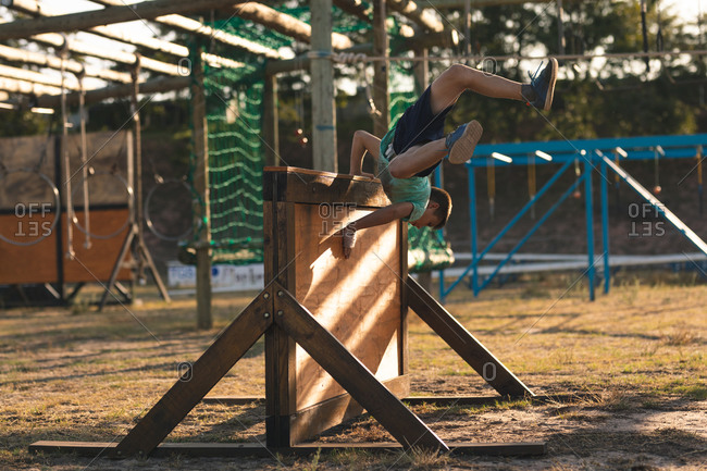 A Caucasian boy wearing a green t shirt and black shorts at a boot camp on a sunny day, vaulting over a wooden fence in an obstacle course