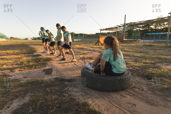 A group of Caucasian boys and girls wearing green t shirts and black shorts at a boot camp on a sunny day, pulling one girl sitting in a tire together with a rope