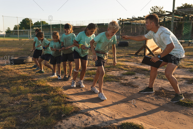 A Caucasian male fitness coach instructing a group of Caucasian boys and girls wearing green t shirts and black shorts at a boot camp on a sunny day, pulling a tire together with a rope