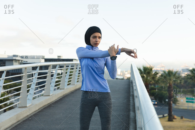 Fit mixed race woman  wearing hijab and sportswear exercising outdoors in the city on a sunny day, stretching her arms on a footbridge. Urban lifestyle exercise.