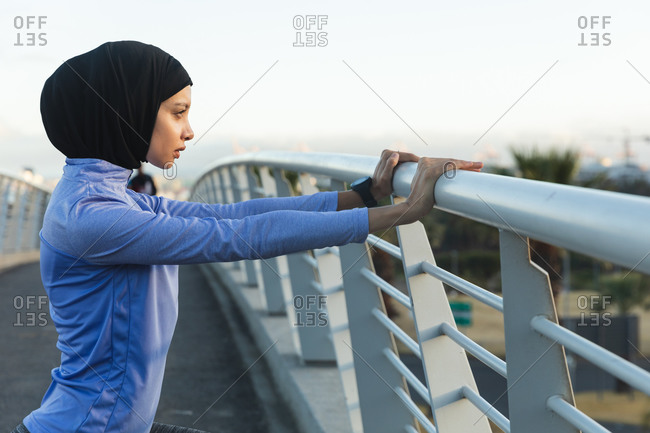 Fit mixed race woman wearing hijab and sportswear exercising outdoors in the city on a sunny day, stretching on a footbridge. Urban lifestyle exercise.